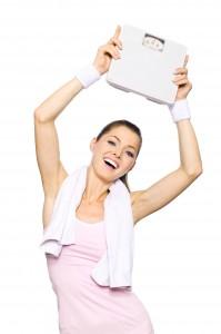 Sportliche Frau mit Waage in der Hand